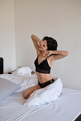 Young brunette woman stretching in her bed at morning - p1607m2183912 by zhushman