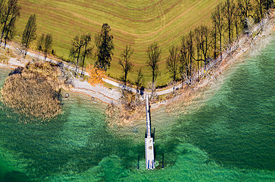 Germany, Bavaria, Kaltenbrunn, Tegernsee, shadows of trees at the lakeshore and jetty, aerial view - p300m2104443 by Martin Siepmann