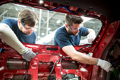 Two colleagues working at bodywork in modern car factory - p300m2144969 von Fotoagentur WESTEND61