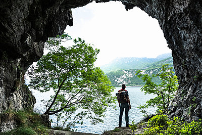 Male hiker looking at Lake Como against sky from cave entrance - p300m2198620 by 27exp