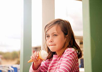 Girl (5-7) eating ice cream, Southwold, Suffolk, United Kingdom - p300m2298857 von LOUIS CHRISTIAN