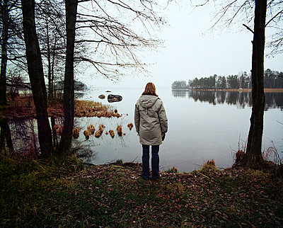 A lonely woman by a lake Sweden. - p31221638f by Per Eriksson
