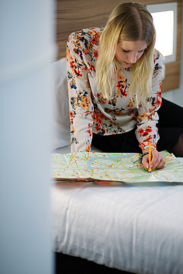 United Kingdom, England, London, Young woman examining map on bed - p352m1079719f by Jonne Heinonen