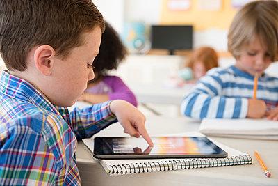 Student using digital tablet in classroom - p555m1305896 by JGI/Jamie Grill