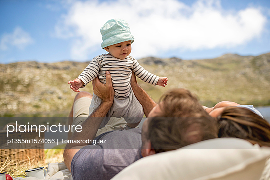 Junge Familie macht ein Picknick - p1355m1574056 von Tomasrodriguez
