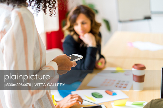 Female entrepreneur using smart phone in board room at office - p300m2264479 by VITTA GALLERY