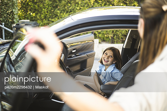 Portrait of mother, father and two daughters standing by car at electric vehicle charging station - p426m2298432 by Maskot