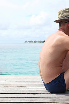Man sitting on boardwalk - p045m668523 by Jasmin Sander