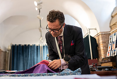 Serious male tailor selecting material - p1166m2261413 by Cavan Images
