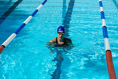 Female swimmer standing in swimming pool - p1315m2090984 by Wavebreak