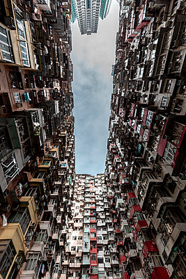 Hong Kong, Quarry Bay, apartment blocks contrasting with modern skyscraper - p300m2069665 by Daniel Waschnig Photography