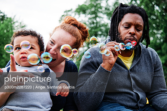 Father blowing bubbles while playing with family at park - p300m2287220 by Angel Santana Garcia
