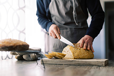 Man cutting a fresh loaf of bread for lunch. - p1166m2192120 by Cavan Images