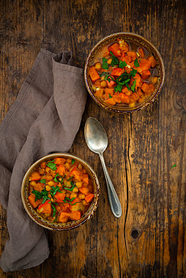 Two bowls of spicy oriental pumpkin stew with chick-peas, parsley and Hokkaido squash - p300m2155539 by Larissa Veronesi