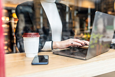 Close-up of businesswoman using laptop at a cafe in the city - p300m2181206 by William Perugini