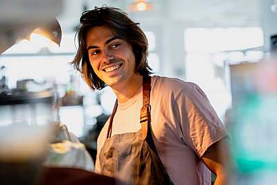 Smiling male owner looking away while working in coffee shop - p300m2202758 by Kniel Synnatzschke
