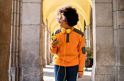 Cheerful woman with mobile phone and headphones looking away while walking at corridor - p300m2252609 by Jose Carlos Ichiro