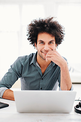 Man with Afro hairstyle working on laptop - p586m1011164 by Kniel Synnatzschke