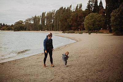 Mother and baby walking on beach, Wanaka, Taranaki, New Zealand - p924m2098085 by Peter Amend
