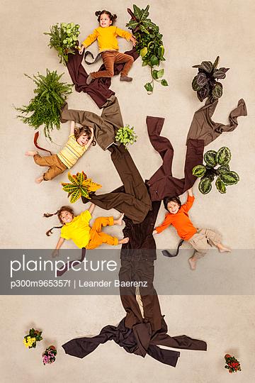 Children playing monkeys in tree - p300m965357f by Leander Baerenz