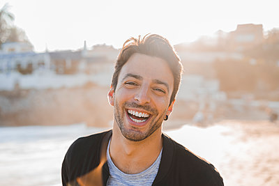 Portrait of laughing young man with stubble on the beach at sunset - p300m1567678 by VITTA GALLERY