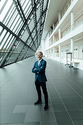 Smiling senior businessman with arms crossed standing in corridor at office - p300m2266308 by Gustafsson