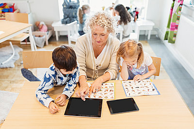 High angle view of senior teacher and children with animal charts and digital tablets - p426m1131054f by Maskot