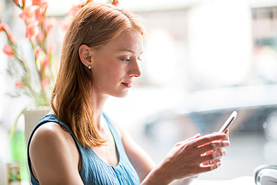 Woman using smartphone in office - p429m2077885 by Tamboly
