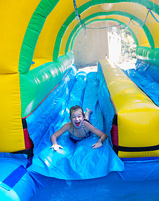 Caucasian girl laughing on water slide - p555m1415313 by Marc Romanelli