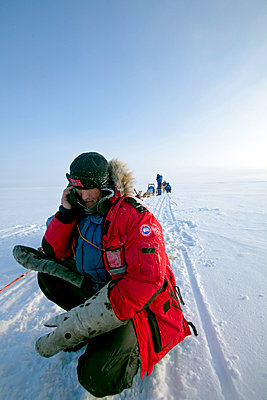 Norway, Finnmark Region. Dog sledding in the Arctic Circle - an explorer stops his husky team to make a phone call on a frozen lake - p6521452 by Mark Hannaford