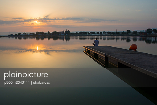 Relaxed girl on the floating platform on the lake at sunrise - p300m2043111 von skabarcat