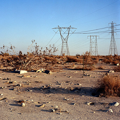 Desert ground with electricity pylons in background - p1094m900159 by Patrick Strattner