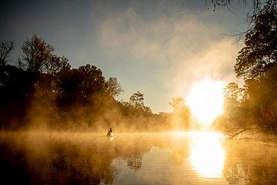 Sunrise canoe ride on foggy river. - p1166m2269648 by Cavan Images