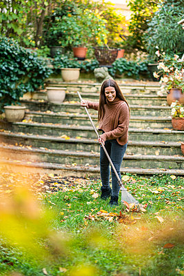 Woman in warm clothing sweeping with rake in back yard garden - p300m2250255 by Annika List