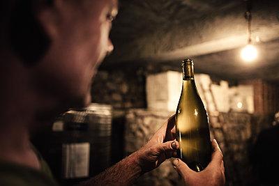 Winemaker gazing at wine bottle in cellar - p429m1226851 by heshphoto