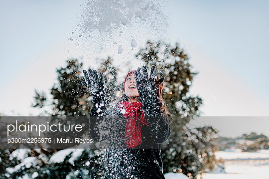 Playful woman throwing snow while enjoying winter at countryside against clear sky - p300m2256975 by Manu Reyes