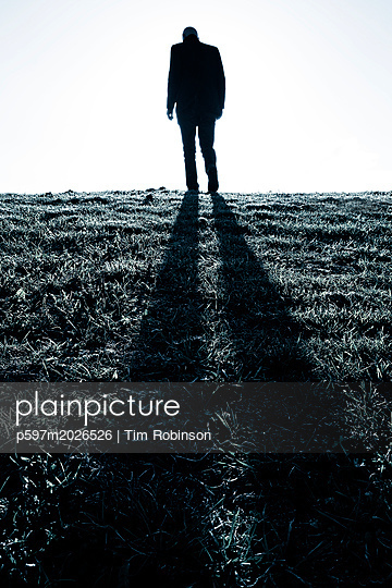 Silhouette of man walking over grass field - p597m2026526 by Tim Robinson
