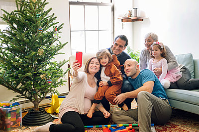 Pregnant woman taking selfie while sitting with family by Christmas tree at home - p1166m1210370 by Cavan Images