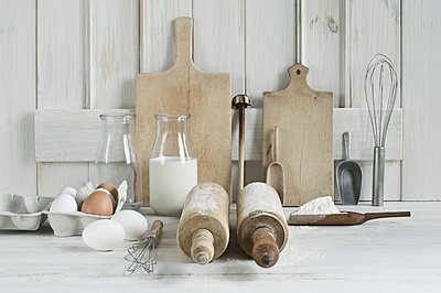 Kitchen utensils, rolling pin, wire whisk, shovel, chopping board, eggs, flour and milk - p300m1587381 von Achim Sass