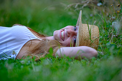 Portrait of laughing teenage girl wearing straw hat lying on a meadow in summer - p300m2080803 by Lisa und Wilfried Bahnmüller
