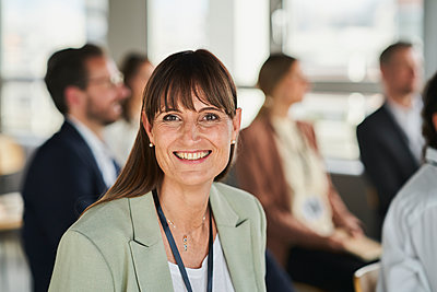 Smiling female entrepreneur with colleagues at educational event - p300m2281425 by Annika List