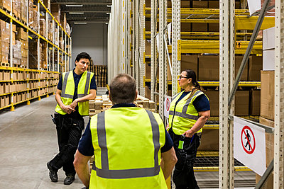 Multi-ethnic coworkers discussing while standing by racks at distribution warehouse - p426m2018842 by Maskot