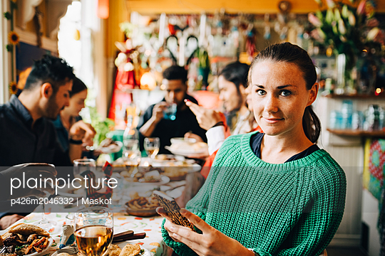 Portrait of confident young woman holding smart phone while sitting with friends at table in restaurant during dinner pa - p426m2046332 by Maskot