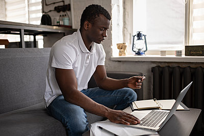 Black man making online order on couch - p1166m2235016 by Cavan Images