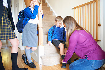 Woman putting on son's school shoe on stairs - p429m1504607 by Peter Muller