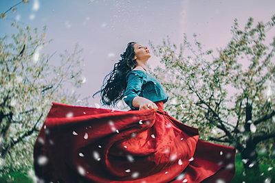 Caucasian woman dancing near flowering trees - p555m1491491 by Kateryna Soroka