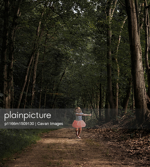 Girl dancing on dirt road amidst forest - p1166m1509130 by Cavan Images