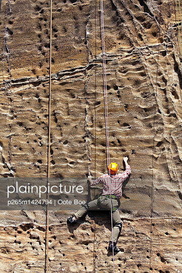 Man free climbing on steep face - p265m1424794 by Oote Boe