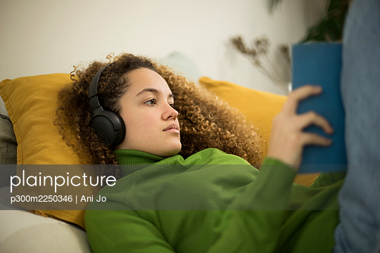 Young woman with book lying on bed while listening music through headphones at home - p300m2250346 by Ani Jo