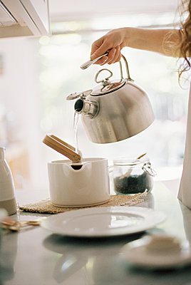 Woman standing in a kitchen pouring hot water from a kettle into a tea pot. - p1100m1080251 by Mint Images